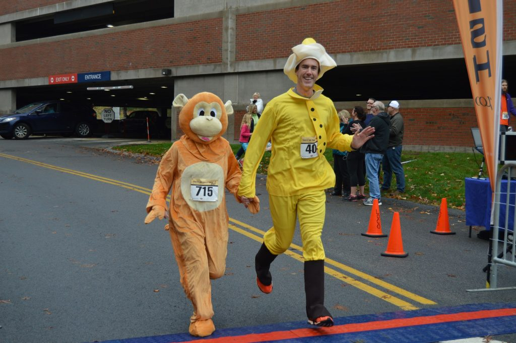 Richard Feeney, DO, Core Physiatry, crosses the finish line at this year's Trick or Treat Trot.